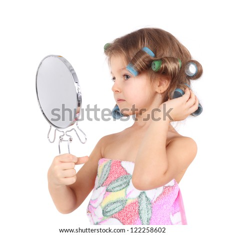 cute funny little girl in the curlers looking at the mirror - stock photo