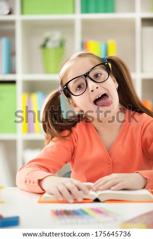 cute funny little girl  stops homework reading to stick her tongue out