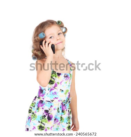 cute funny little girl wearing the curler with the mobile phone - stock photo