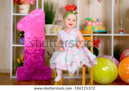 Cute funny little kid in first birthday with colored balloons in the bright room  laughing  - stock photo