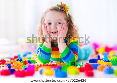 Cute funny preschooler little girl in a colorful shirt playing with construction toy blocks building a tower in a sunny kindergarten room - stock photo