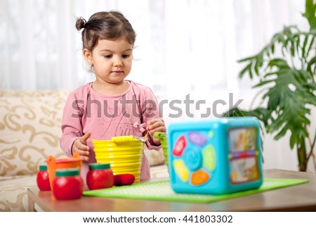 Cute funny preschooler little girl  playing with toys in room, Children at day care