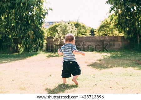 Cute funny smiling baby making his first steps in a sunny summer garden