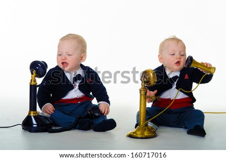 cute funny twin babies wearing tuxedos conversing on old-fashioned telephones - communications concept - stock photo