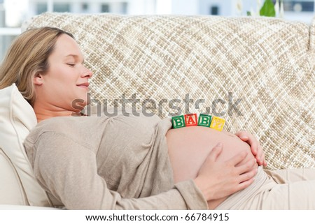 Cute future mom with baby letters on the belly in the living room - stock photo