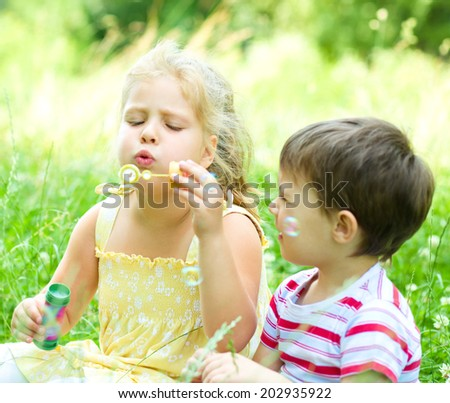 Cute girl and boy blowing soap bubbles, outdoors