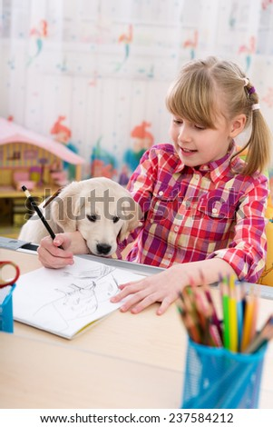 Cute girl and puppy drawing together at kids room