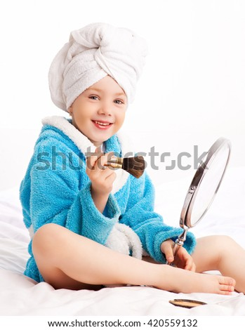 cute girl applying makeup on her face ,wearing a bathrobe and a towel after shower in bed at home - stock photo