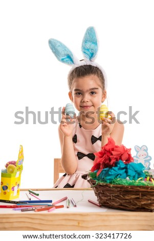 Cute girl at table showing colorful Easter eggs isolated on white background - stock photo