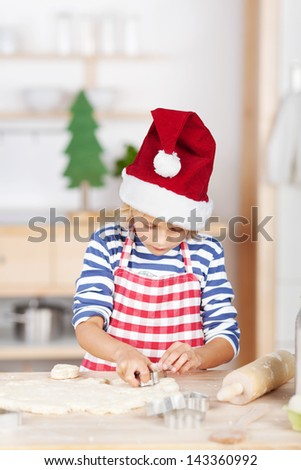 Cute girl baking Christmas cookies cutting the pastry with a cookie cutter in her red striped apron and Santa hat - stock photo
