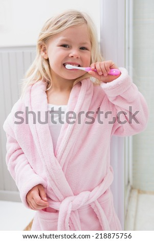 Cute girl brushing her teeth at home in the bathroom - stock photo
