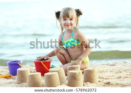 Cute girl building sandcastle on beach