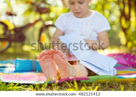 Cute girl child sitting on grass with book. Foots in focus