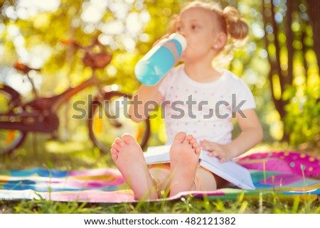Cute girl child sitting on grass with bottle. Foots in focus