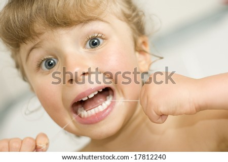 Cute girl cleaning teeth by floss in bath - stock photo