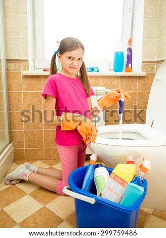 Cute girl cleaning toilet with disgust
