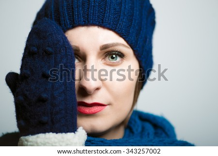 Cute girl closes one eye with his hand, dressed in winter clothes, bright lifestyle photo, isolated on a gray background