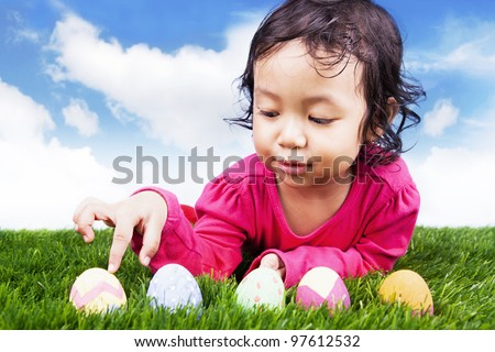 Cute girl counting easter eggs using her finger on the green grass - stock photo