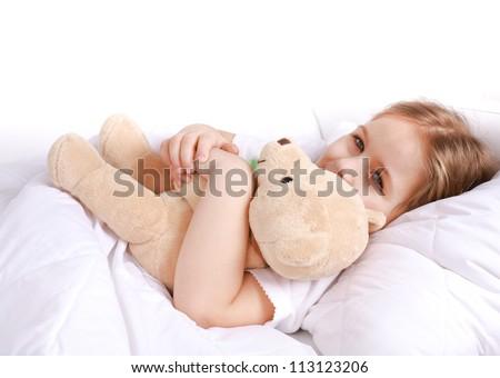 Cute girl cuddling with teddy bear to sleep - stock photo