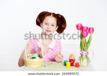 Cute girl decorates Easter eggs, on light background