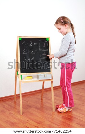 Cute girl doing the math on chalkborard - stock photo