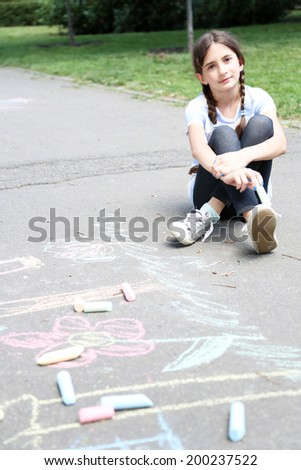 Cute girl drawing with chalk on asphalt - stock photo