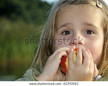 Cute girl eating apple in outdoor portrait - stock photo