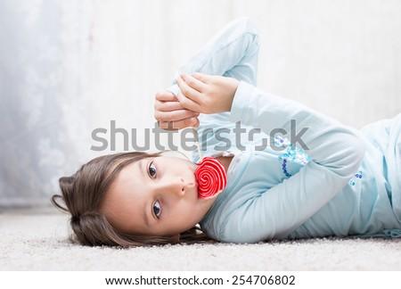 cute girl eating sugar candy - stock photo