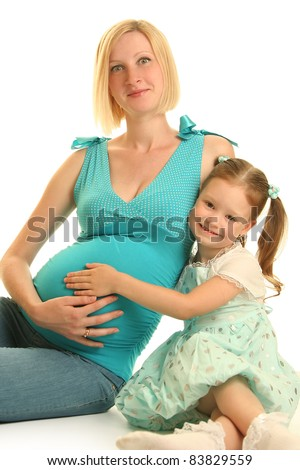 cute girl embracing her pregnant mother - stock photo
