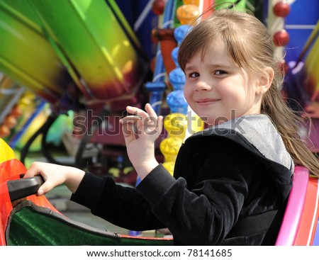 Cute girl fun on a carousel - stock photo