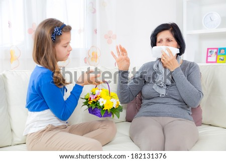 Cute girl giving a bunch of flowers to her grandmother.Grandmother has an allergy to flowers. - stock photo