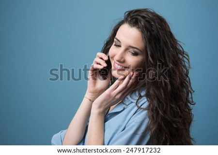 Cute girl having a phone call with her smart phone and touching her cheek - stock photo