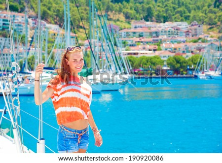 Cute girl having fun in yacht harbor, enjoying sunny summer day, active lifestyle, traveling on luxury water transport - stock photo