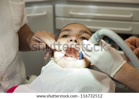 Cute girl having her teeth checked by doctor