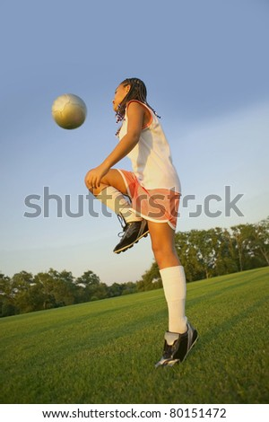 Cute girl hitting soccer ball with knee.