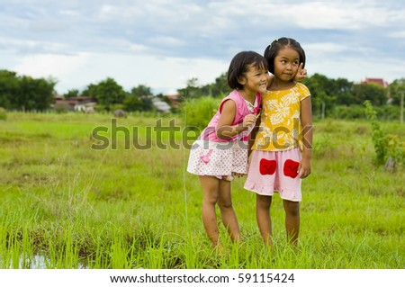 cute girl holding a grasshopper in her hand showing her friend something