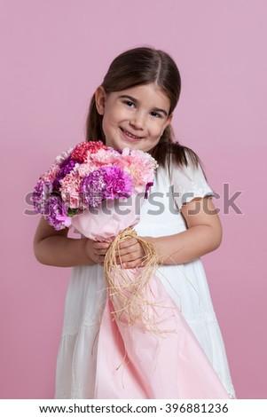 Cute girl holding flowers - stock photo