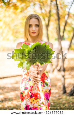 Cute Girl holding in hands green maple leaves Young adult woman wear colorful dress with flowers pattern Female stand outdoor against yellow autumn park Empty copy space for inscription