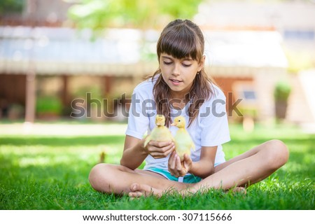 Cute girl holding two spring ducklings outdoors  - stock photo
