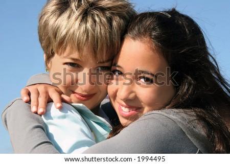 Cute girl hugging her mother on a sunny day - stock photo