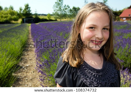 Cute girl in a field of colorful purple lavender. - stock photo