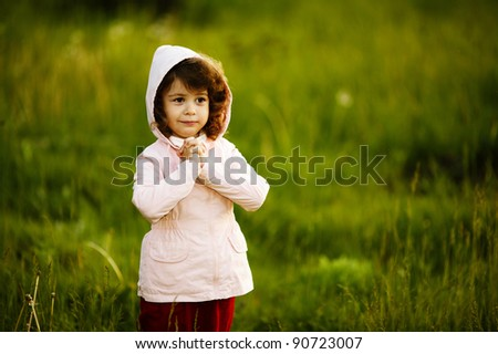 cute girl in a hood with curls - stock photo