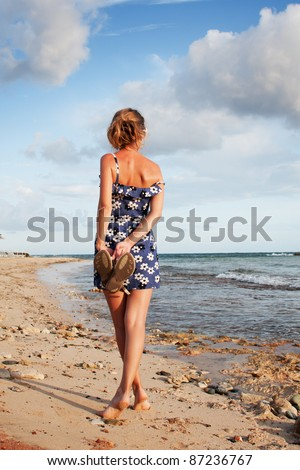 Cute girl in beautiful dress standing on the beach - stock photo