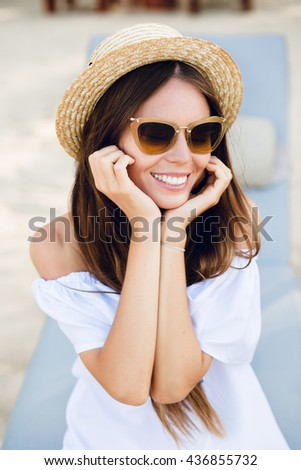 Cute girl in brown sunglasses and straw hat smiles widely and holds her hands near chin. She wears white dress with open shoulders. She sits on a beach chaise-longue. - stock photo