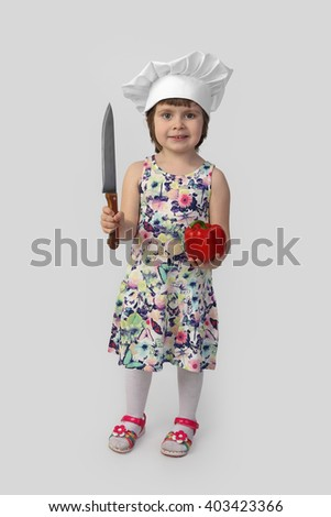 Cute girl in chef hat with big knife and red paprika in hand stands full height on gray background - stock photo