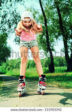 Cute girl in roller skates at a summer park. - stock photo