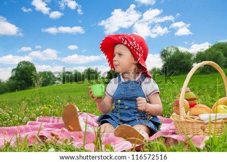 cute girl in ted hat drinking from the green cup on picnic - stock photo