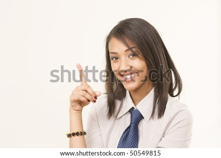 Cute girl in tie pointing at copy space and smiling - stock photo
