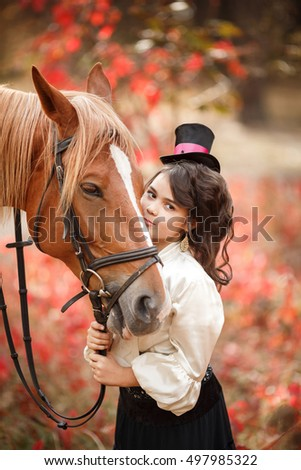 Cute girl in vintage stylized suit with a horse.