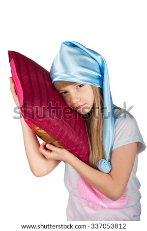 Cute girl in white and pink pajamas and blue sleeping hat  standing with pink pillow isolated on white - stock photo